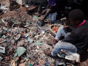 Workers harvest copper from electrical circuit boards