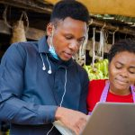 Young African business man shows a market woman some information on his laptop.